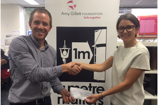 Bike Chaser co-founder Cameron Nicholls presenting Amy Gillett Foundation CEO Phoebe Dunn with our latest ad revenue donation.