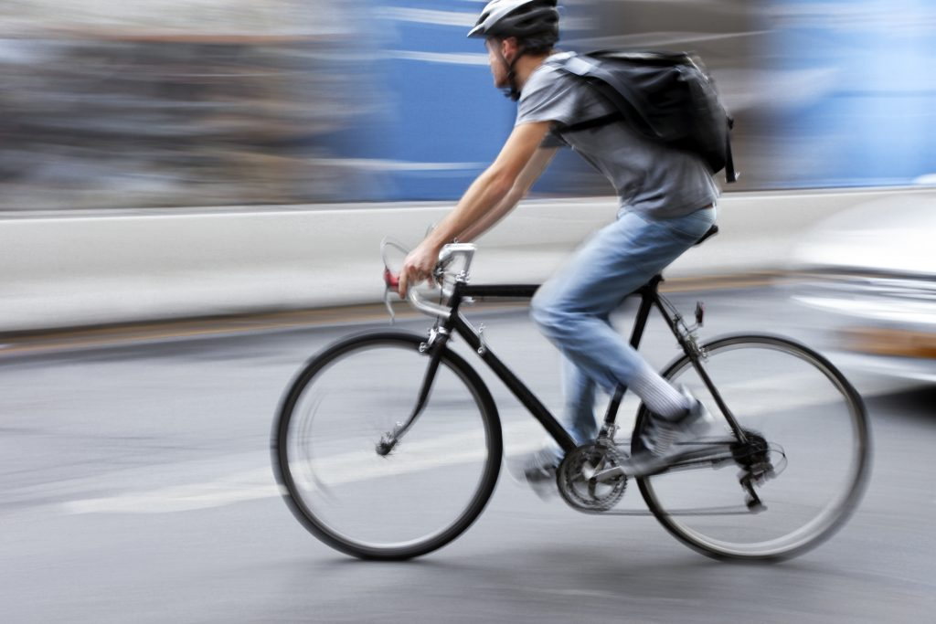 cyclist riding in traffic with helmet